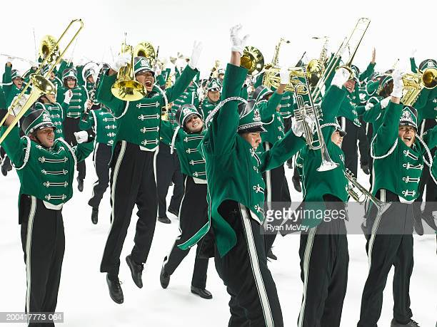 Teenage (14-18) marching band jumping and cheering, arms raised