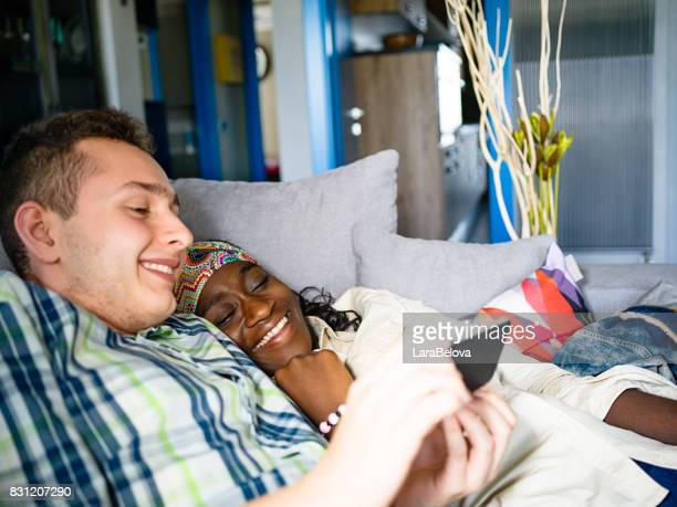 Teenage mixed race couple watching a movie on smart device