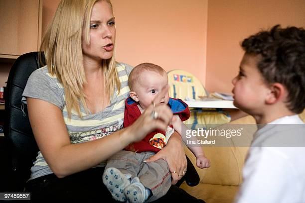 A teenage mother with her two children aged two years old and four months old She is reprimanding her eldest son for throwing a toy at his younger...