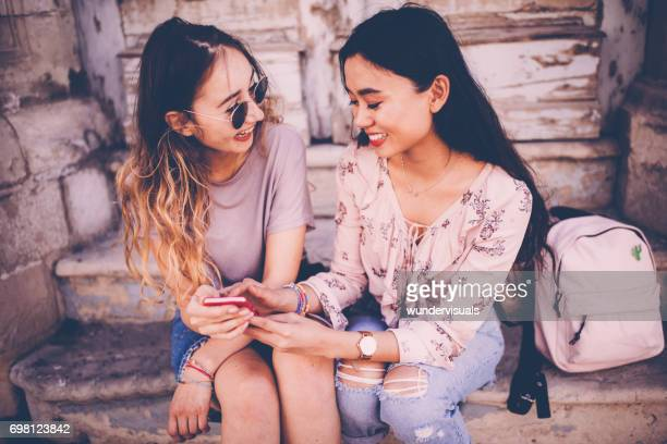 Teenage multi-ethnic hipster girls looking at smartphone screen and laughing