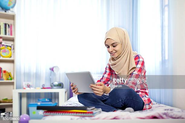 Teenage muslim girl using tablet computer