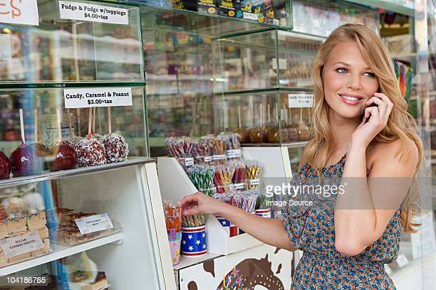 Teenage on cellphone by confectionery stand