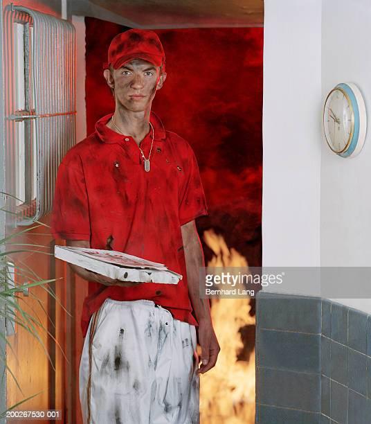 Teenage pizza deliveryman (16-18) in doorway, covered in grime