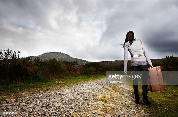 Teenage runaway walks away down deserted road