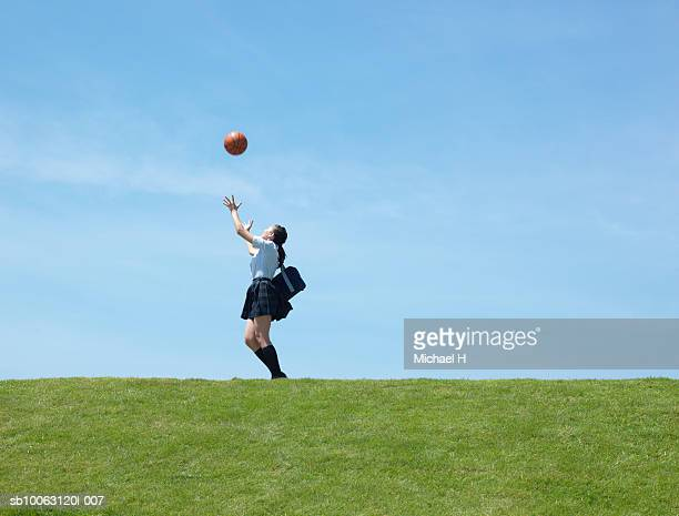 Teenage schoolgirl (16-17) catching basketball on lawn, side view