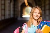 Teenage schoolgirl with books on campus