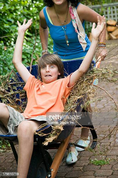 Teenage Siblings Playing With a Wheelbarrow
