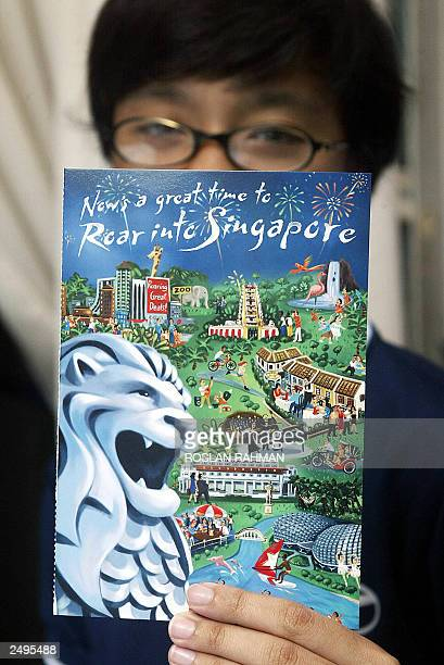 A teenage Singaporean resident shows one of the postcard with overseas postage prepaid given out to Singaporeans permanent residents and foreign...