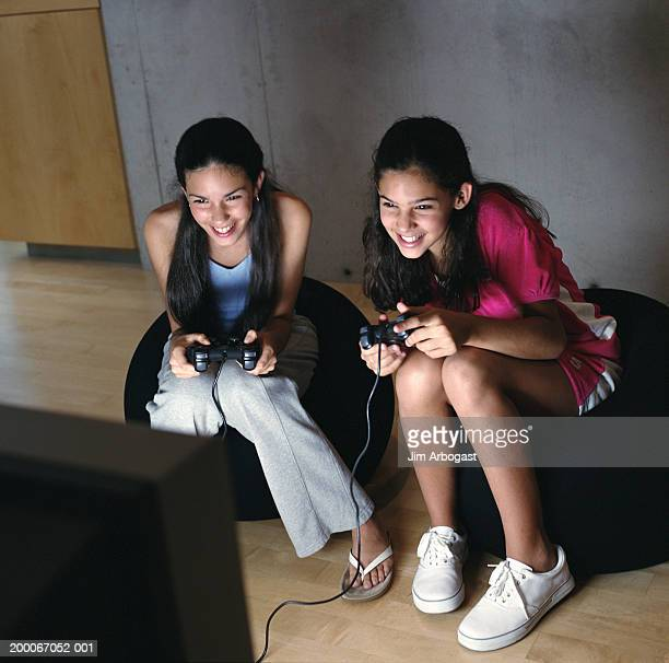 Teenage sisters (12-14) playing video games at home