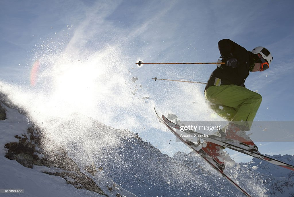 Teenage skier in mid-air jump over mountains