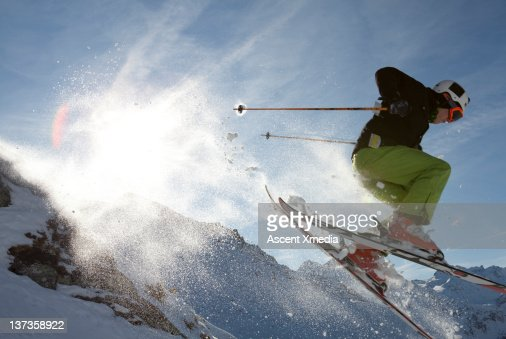 Teenage skier in mid-air jump over mountains : Stock Photo