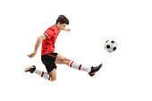 Teenage soccer player kicking a football isolated on white background
