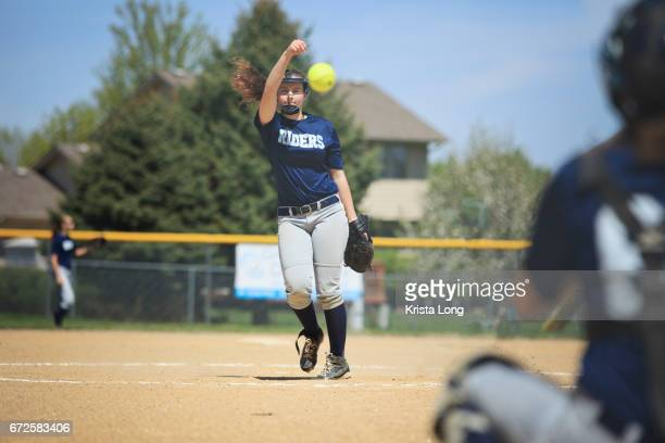 Teenage softball player throwing a pitch.