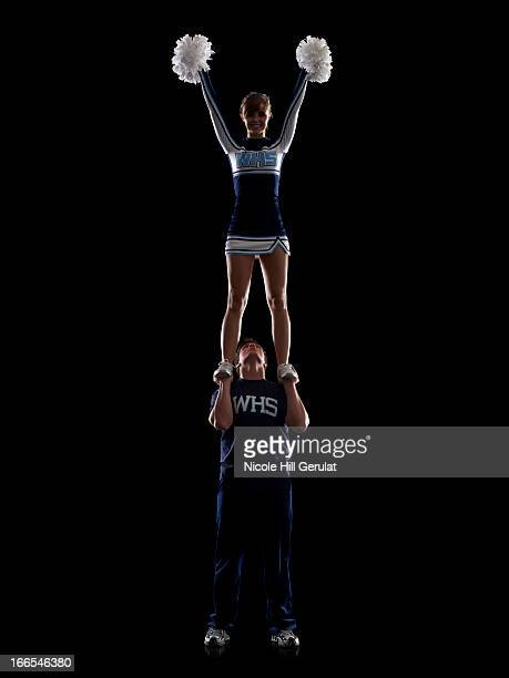 Teenage sportsman(16-17) holding aloft teenage cheerleader girl (16-17)