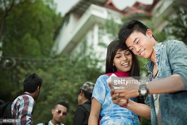Adolescente étudiant amis de diverses origines ethniques partagent smartphone près du campus.