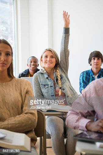 Teenage student raising hand in classroom