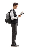 Full length profile shot of a teenage student reading a book and waiting in line isolated on white background
