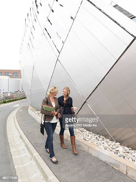 Teenage student & teacher walk in campus setting
