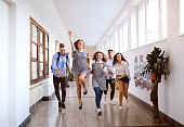 Group attractive teenage students in high school hall jumping high.