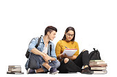 Teenage students seated on the floor studying together isolated on white background