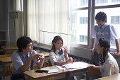 Teenage students (13-18) talking in classroom