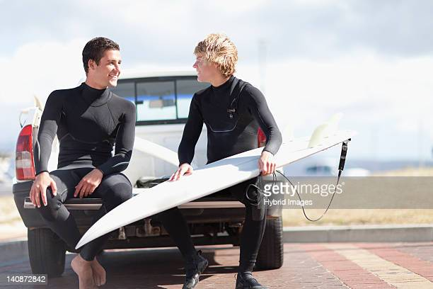 Teenage surfers with board in truck bed