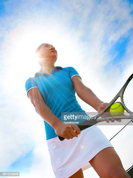 Teenage tennis player serves ball