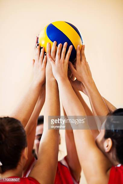 Teenage volleyball team holding the ball up