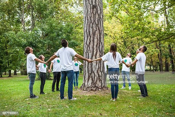 Teenage volunteers standing in circle round tree