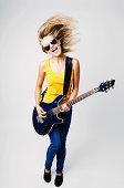 Teenage woman playing on guitar