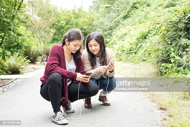Teenaged Eurasian Sisters Playing Augmented Reality Games on Smartphones
