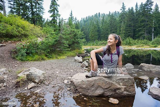 Chica Teenaged excursionistas descanse sobre roca cerca del lago en el bosque