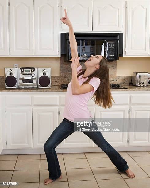 Teenaged girl singing in kitchen