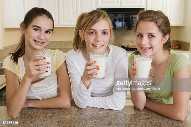 Teenaged girls drinking milk