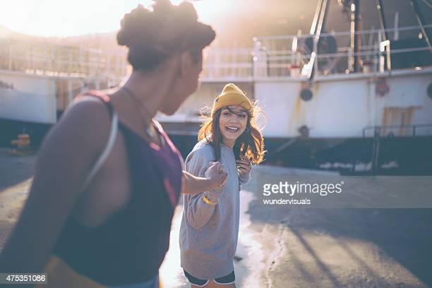 Teenaged grunge ragazza amici tenendo le mani su estate pomeriggio