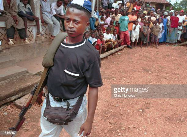 A teenaged RUF rebel solider stands guard during a rally June 9 2001 in the eastern town of Buedo Sierra Leone The RUF infamous for their forced...