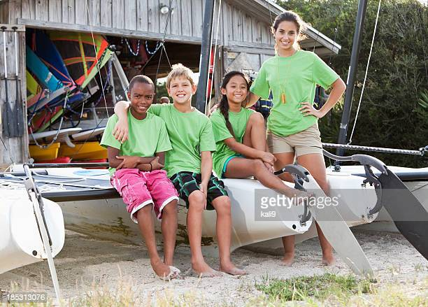 Teenager and children in front of water sports equipment shack