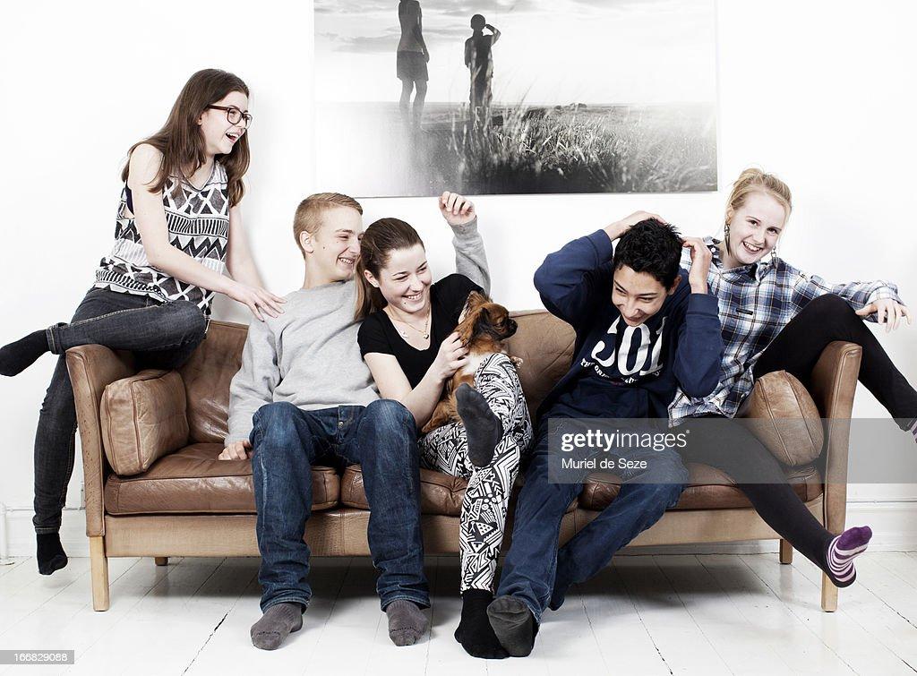 5 teenager and dog on sofa : Stock Photo