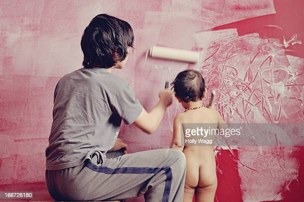 Teenager and toddler child paint wall