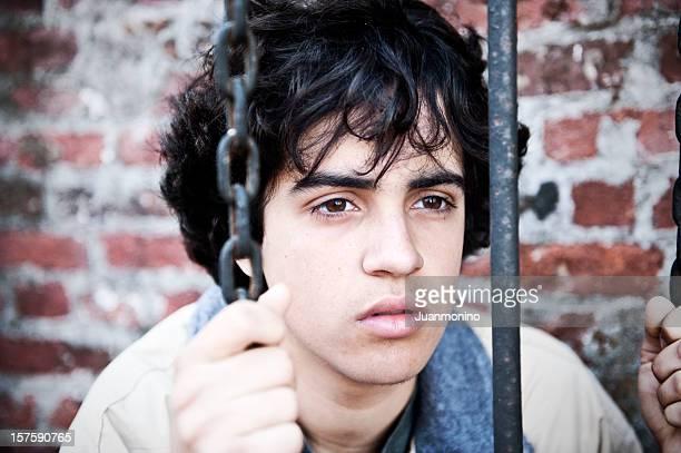Adolescent derrière bars