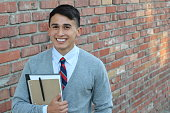 Cute teenager boy in formal high school uniform holding notebooks smiling with copy space.