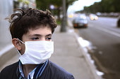 teen boy in protection mask on the highway city background