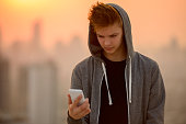 Handsome teenager boy outdoors using mobile phone