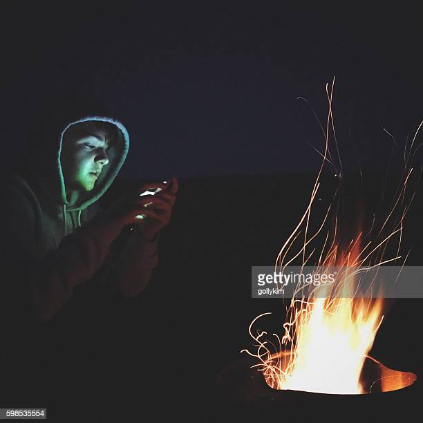 Teenager boy using smartphone by the campfire