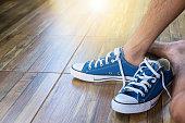 Teenager boy wear blue canvas sneaker , flare effect