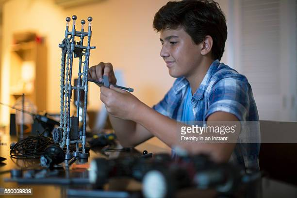Teenager building his science project at home