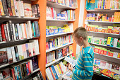 Young boy in a book shop or library browsing a book
