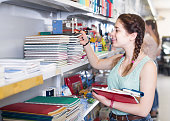 Cheerful italian teenager buying different products in stationery shop