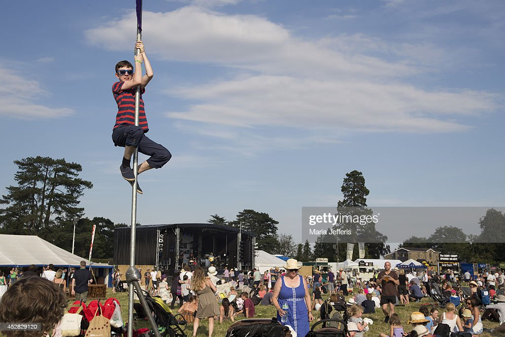 A teenager climbs a flagpole at Deer Shed Festival at Baldersbey Park, Topcliffe on July 25, 2014 in Thirsk, United Kingdom.