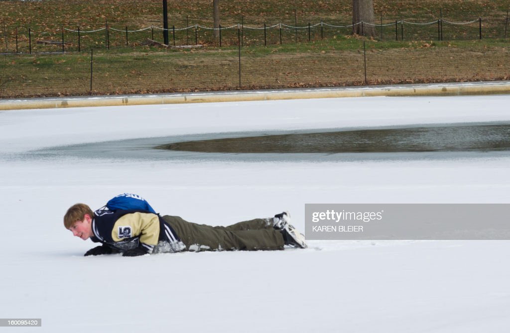 A teenager crawls on the ice on the reflecting pool near the Washington Monument January 26, 2013 in Washington, DC. Below freezing temperatures on the East coast over the past few days have caused some areas of the lengthy pool to freeze over. AFP PHOTO/Karen BLEIER
